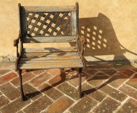 mediterranean house: elegant iron and wood openwork chair on brick paved floor, Tuscany
