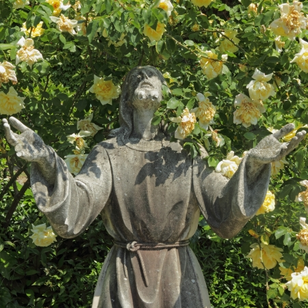 sculpture of Jesus sculpture on tomb with roses photo
