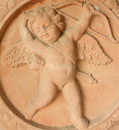 carved cupid with arrow and bow in tuscan terracotta  photo