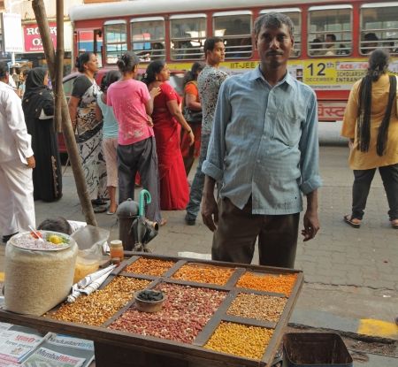 indian fair: MUMBAI, INDIA -NOV 26  Street vendor sells nuts on Nov  26, 2010 in Mumbai, India  According to the Ministry of Housing and Urban Poverty Alleviation, there are 10 million street vendors in India