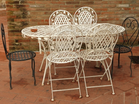white and black ornamental metal garden furniture set on brick paved patio
