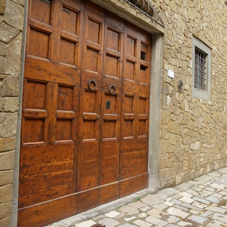 elegant big double doorway facade of old houses in medieval tuscan village, Montefioralle, Greve in Chianti, Italy, Europe photo