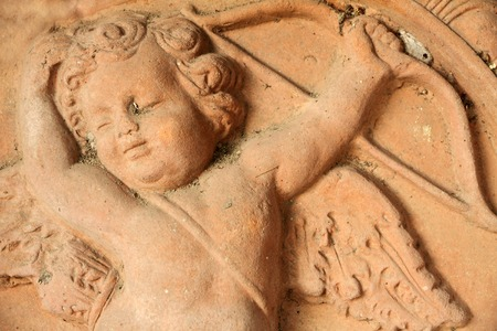 antique relief of cupid  with arrow and bow in tuscan terracotta  photo