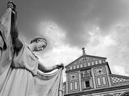 sante: cemetery statue and Basilica di San Miniato al Monte in Florence, monumental cemetery Porte Sante, Italy