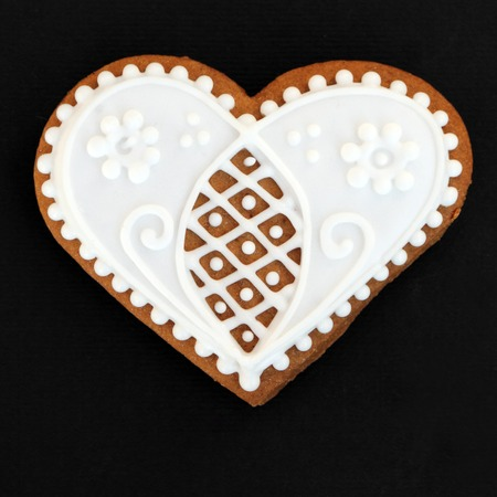 heart shaped gingerbread cookie isolated on black photo