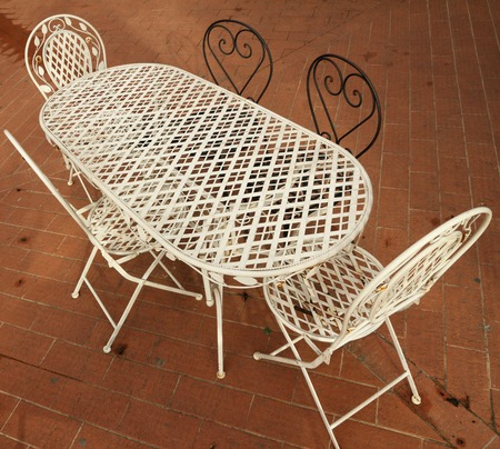 white and black ornamental metal garden furniture set on brick paved patio seen from above photo