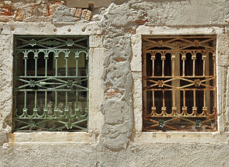lumber room: two old windows with decorative metal grid in Venice