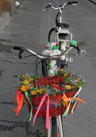 decorated bike: bici con cesto decorato con fiori parcheggiata in strada a Firenze, Toscana
