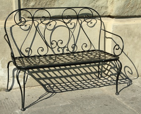 metal ornamental bench on tuscan street, Italy photo