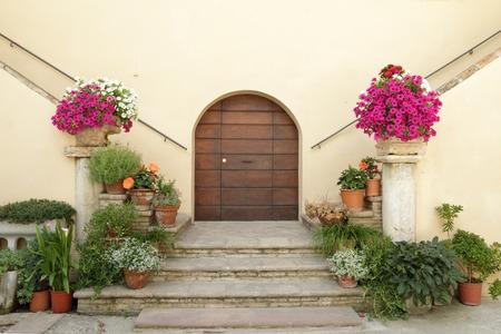 elegant doorsteps to the italian villa decorated with many flowering plants in pots, Spello, Umbria, Italy Archivio Fotografico