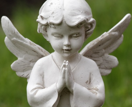praying sweet angel figurine isolated on green background