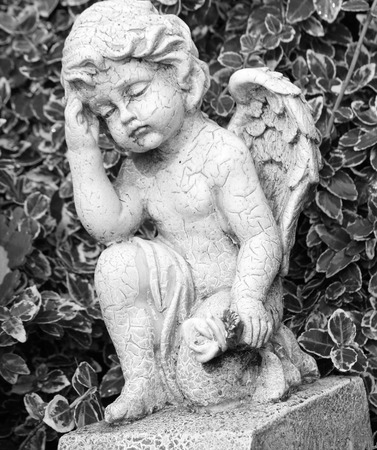 condolence: angel with flower in hand - cemetery sculpture