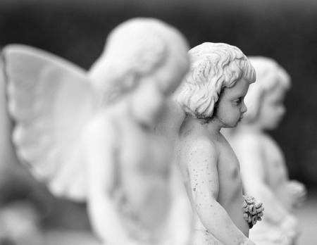 recollection: cemetery angel statues with garlands in hands, Italy