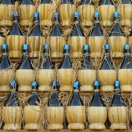 fiasco: arranged many chianti wine bottles  ( traditionally in straw basket, called fiasco, plural fiaschi ),Florence, Tuscany, Europe