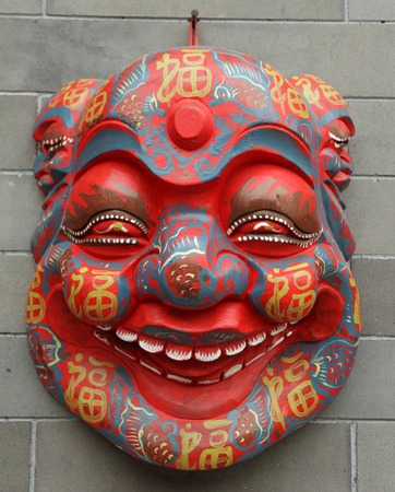 painted face mask: chinese mask on wall on Liulichang street in Beijing, China Stock Photo