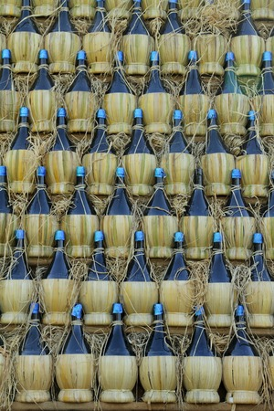 fiasco: wall made of many chianti wine bottles ( traditionally in straw basket, called fiasco, plural fiaschi ),Florence, Tuscany,Italy, Europe