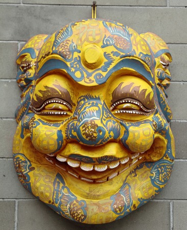hypocritical: chinese mask on wall on Liulichang street in Beijing, China Stock Photo