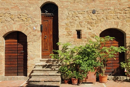 tuscan house: picturesque old wall with doors in tuscan village Pienza, Italy