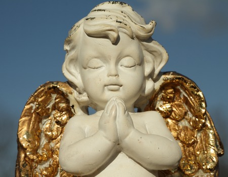 angel figurine: praying little angel figure with golden wings isolated on sky