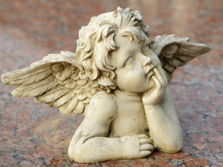 angel figurine: decorative sculpture of putto isolated on granite surface