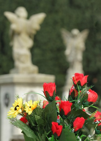wistfulness: bouquet with red roses on old cemetery with angelic statues on the background, Italy Stock Photo