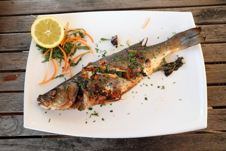 sea bass: Grilled sea bass Fish plate on wooden table  ,serving in maltese  restaurant