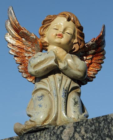 thoughtfulness: angelic sweet figurine with colorful wings isolated on blue sky Stock Photo