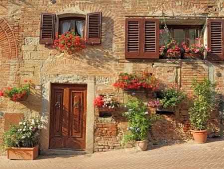 beautiful doorway to the tuscan house decorated with many flowering plants, Italy, Europe Archivio Fotografico