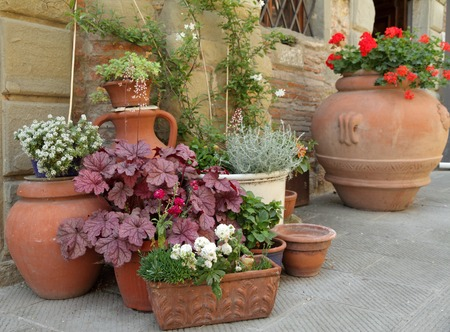 planters: various traditional clay planters with decorative plants on italian narrow street,Europe Stock Photo