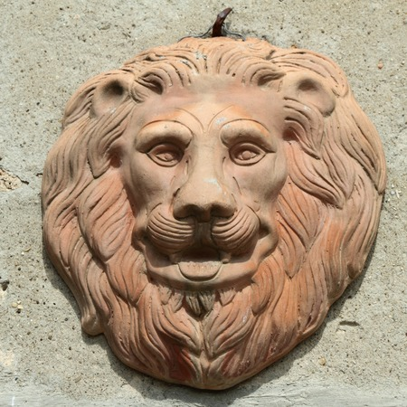 terracotta: decorative lion head in terracotta hanging on wall, Tuscany, Italy