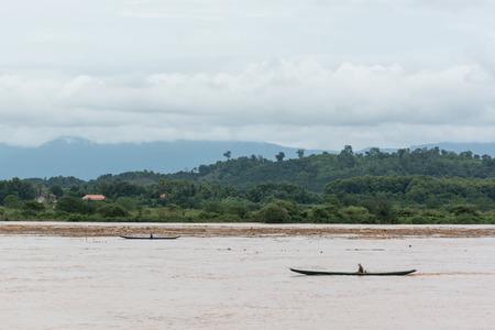 recoger: dos barcos de motor recogen troncos en el río después de las inundaciones en el río Khong