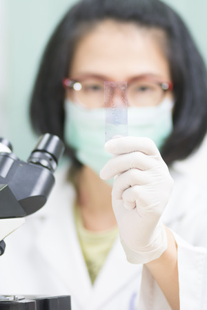 microscope slide: Short hair young female scientist analyzing and show microscope slide in medical lab