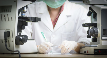 cancer screening: scientist hold slide in left hand and write something down on piece of white paper by right hand in laboratory with vignetting effect
