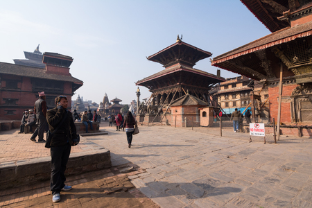 3rd ancient: KATHMANDU,NEPAL -5 JAN : Undentified man use mobile in tourist attraction Patan Durbar Square in napel on January 5,2016