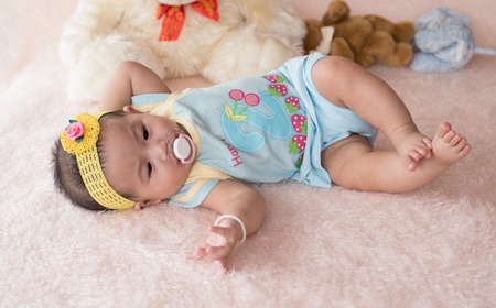 generration: little child on blue shirt lay down on soft bed with pacifier in mouth
