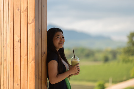 spiritless: Beautiful asian women hold  cup of ice mocha green tea coffee in open air coffee shop with tea plantation background