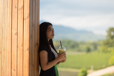 Beautiful asian women hold  cup of ice mocha green tea coffee in open air coffee shop with tea plantation background