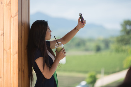 Beautiful asian women hold  cup of ice mocha green tea coffee in open air coffee shop with mobile phone in hand and selfie Stock Photo