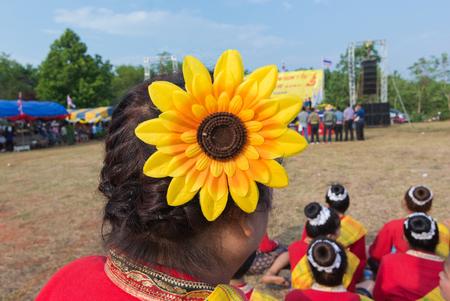 folwer: Big yellow plastic folwer decorated on woman head in wax festival,northeast Thailand.