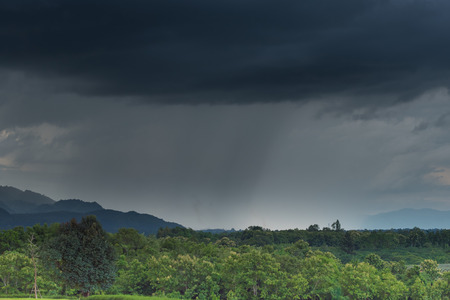 monsoon clouds: Blurry of rain storm over the mountain.