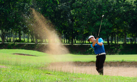 shot: Golfers hit the ball in the sand. Speed and Strength Stock Photo