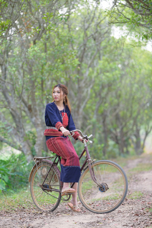 Young asian women sitting on an old bike in tribe dress in rice field area.Thailand. Stock Photo