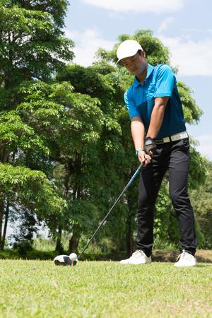 putt: Handsome asian golfer man putt golf . Stock Photo
