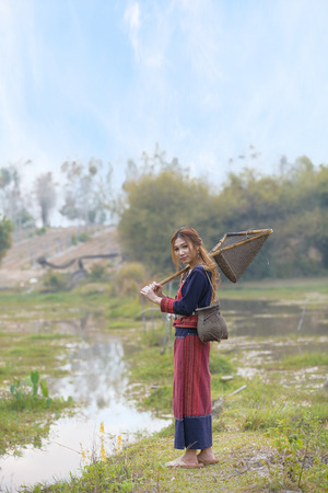 fishing gear: Asian beautiful lady in tribe dress stand near swamp with fishing gear in hand.Thailand Stock Photo