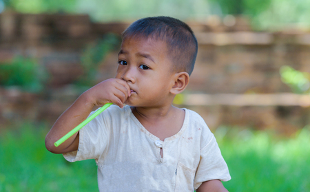 innocent: Asian boy with straw in mouth,dirty with innocent play.