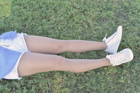 belongs: Hop and legs in jeans and leging belongs to beautiful girl lay down on green grass.