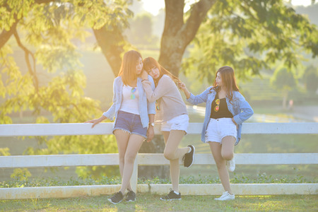 lady's: Three asian young ladys in casual dress enjoy afternoon heat in garden .