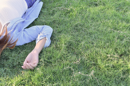 Asian girl lay on grass and rise hand dress in jeans.freedom concept Stock Photo