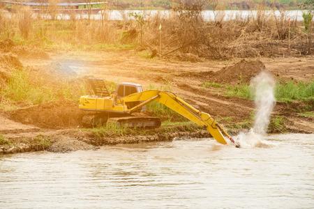 retractable: Shovel bucket on river bank , lift loads, construction machinery, construction machinery manipulator, unloading cargo, hydraulic capture truck, farm equipment, heavy tractor yellow