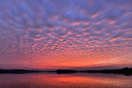 Beautiful sunset sky with colourful altocumulus clouds with reflexion over the lake,natural background,photo texture Stock Photo